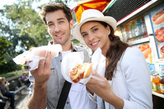 Couple of tourists eating fastfood on travel. Tourists in New York city eating hot dogs Stock Images