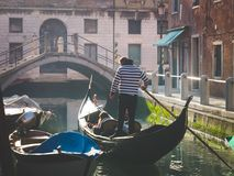 Couple of tourists enjoying gondola tour in the water channel of. Venice Stock Photos