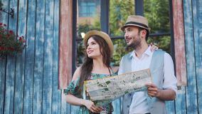 Couple of tourists are exploring the map in travel. a young woman and a man walk around the city on a trip.  stock video footage