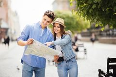 Young Couple of tourists is exploring new city together. Smiling and look at the map on the city street. Couple of tourists is exploring new city together royalty free stock images