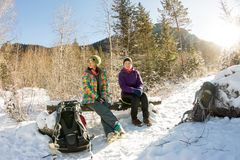 Couple tourists girls sitting on a bench in the winter and looking at the mountains Royalty Free Stock Image