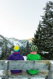 Couple tourists girls sitting on a bench in the winter and looking at the mountains Royalty Free Stock Photos