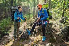 Couple of tourists hiking at the mountain forest. Real people tr Stock Photos