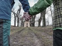Couple tourists hold hands, walking in alley. Couple tourists hold hands and walking through alley in park, old chapel at the end young wrist women weather trust stock photo