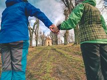 Couple tourists hold hands, walking in alley. Couple tourists hold hands and walking through alley in park, old chapel at the end young wrist women weather trust royalty free stock photography