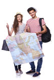 Couple of tourists holding map. Full length of young couple of tourists holding a map and gesturing thumbs up, over white background Royalty Free Stock Photography