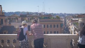 A couple of tourists looking on a map, the city panorama of Rome. 4k stock video footage