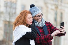 Couple of tourists makes selfy on smart-phone. Man and woman looking for city map in telephone. Urban couple make video chatting. royalty free stock images