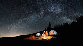 Couple tourists near campfire and tents under night sky full of stars and milky way Royalty Free Stock Photos
