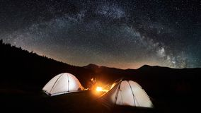 Couple tourists near campfire and tents under night sky full of stars and milky way Royalty Free Stock Images