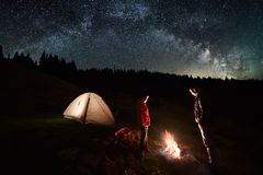 Couple tourists near campfire and tents under night sky full of stars and milky way Stock Photo