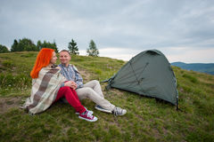 Couple tourists near the tent in the mountains. Happy couple backpackers covered with a plaid sitting on a hill near the camping and looking into the distance Royalty Free Stock Images