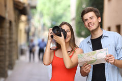 Couple of tourists photographing landmarks. Joyful couple of tourists male and female photographing landmarks with a dslr camera in the street of an old town Royalty Free Stock Photo
