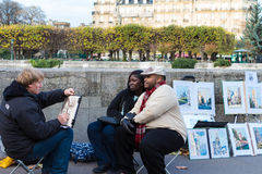 Couple of tourists posing for street painter, paris, France. Stock Photo