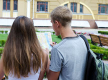 Couple of tourists reading a map. Rear over the shoulder view of a couple of young tourists reading a map in an urban environment Stock Images