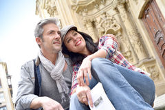 Couple of tourists relaxing by religious monument Stock Photos