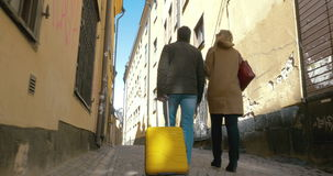 Couple of tourists with roll-on bag walking in old. Steadicam low angle shot of a man and woman with yellow rolling bag walking along the narrow cobbled street stock video