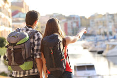 Couple of tourists sightseeing. Back view of a couple of tourists sightseeing in a travel destination with a port with colorful buildings in the background Royalty Free Stock Images
