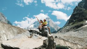Couple of tourists sit on a rock and study a map, plan a route in a mountain hike. royalty free stock photography