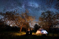 Couple tourists sitting at a campfire near tent under trees and beautiful night sky full of stars and milky way. Romantic couple tourists sitting at a campfire Stock Photo