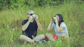 A couple of tourists are sitting on the grass and drinking tea from mugs and talking. Overall plan stock video footage