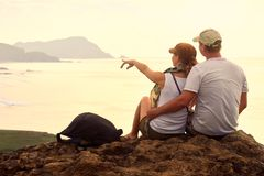 Couple of tourists sitting on hill plan trip to distant islands. Royalty Free Stock Image