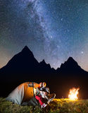 Couple tourists sitting near tent and campfire, looking to the shines starry sky and Milky way in the camping at night Stock Images