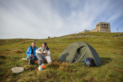 Couple of tourists sitting near tent, cooking breakfast Royalty Free Stock Photos