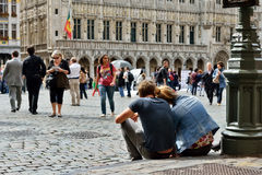 Couple of tourists sitting on the pavement of Grand Place in Brussels Royalty Free Stock Photos