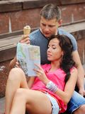 Couple of tourists sitting on steps, reading map. Young couple of tourists sitting on steps, reading map Stock Image