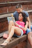 Couple of tourists sitting on steps, reading map. Stock Photo