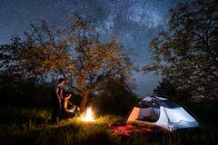 Couple tourists standing at a campfire near tent under trees and beautiful night sky full of stars and milky way. Romantic couple tourists standing at a campfire Royalty Free Stock Images