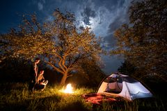 Couple tourists standing at a campfire near tent under trees and night sky with the moon. Night camping Royalty Free Stock Photography