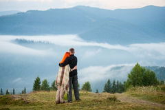 Couple tourists standing on a hill enjoying a morning haze Stock Image