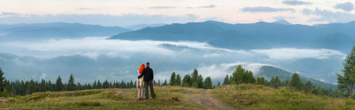 Couple tourists standing on a hill enjoying a morning haze Stock Photography