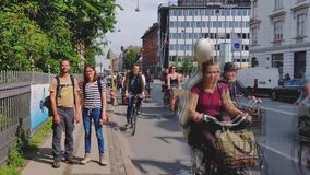 Couple of tourists are standing on sidewalk. Rush hour in Copenhagen center. Many cyclists are riding by. Copenhagen, Zealand / Denmark - June 11 2019: Couple stock footage