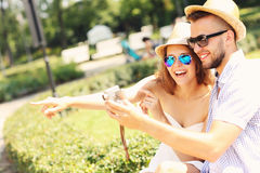 Couple of tourists taking pictures in the park Royalty Free Stock Image