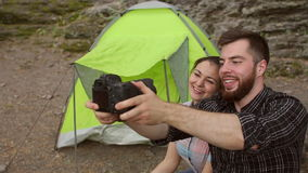 Couple of tourists taking a selfie near the tent. stock video footage