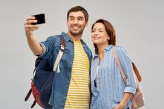 Couple of tourists taking selfie by smartphone. Travel, tourism and vacation concept - happy couple of tourists with backpacks taking selfie by smartphone over royalty free stock images