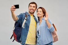 Couple of tourists taking selfie by smartphone. Travel, tourism and vacation concept - happy couple of tourists with backpacks taking selfie by smartphone over royalty free stock photos