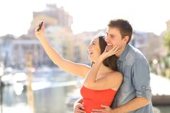 Couple of tourists taking selfies on summer vacation. Happy couple of tourists taking selfies with a smart phone on summer vacation Stock Image