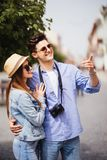 Young Couple of tourists taking a walk in a city street sidewalk in a sunny day Royalty Free Stock Photo