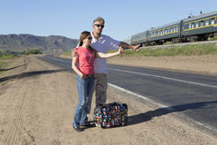 Couple of tourists travel the world hitchhiking Stock Photography