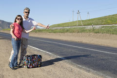 Couple of tourists travel the world hitchhiking Stock Image