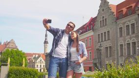 Couple of tourists traveling and exploring beautiful old town. Loving man and woman in a vacation trip. Couple of tourists traveling and exploring beautiful old stock video footage