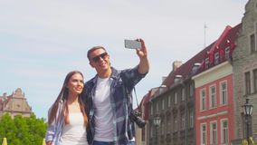 Couple of tourists traveling and exploring beautiful old town. Loving man and woman in a vacation trip. Couple of tourists traveling and exploring beautiful old stock video