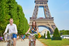 Couple of tourists using bicycles in Paris, France. Young romantic couple of tourists using bicycles near the Eiffel tower in Paris, France Stock Photography