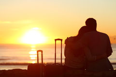Couple of tourists on vacations watching sun Stock Photo