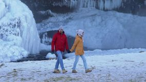 A couple of tourists walk around the glacier.  stock footage