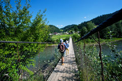 Couple of tourists walk on the suspended wooden bridge over a mountain river Stock Photography